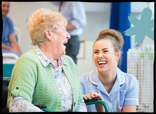Eine Pflegerin hockelt neben einer älteren Patientin, die beiden lachen miteinander.