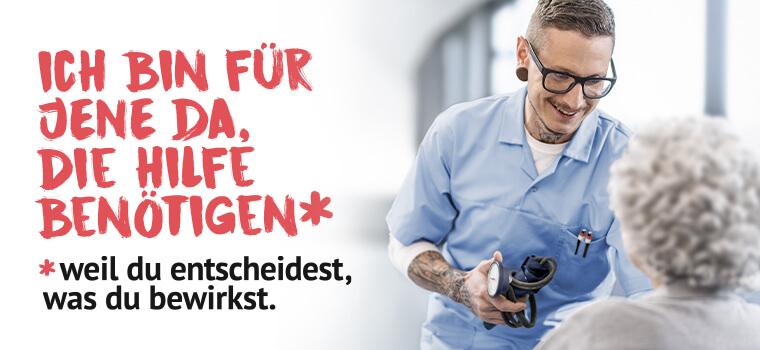 Ich bin für jene da, die Hilfe benötigen - ein Krankenpfleger mit Brille und einem Blutdruck-Messgerät in der Hand spricht lächelnd zu einer vor ihm sitzenden Frau mit lockigem, grauen Haar.